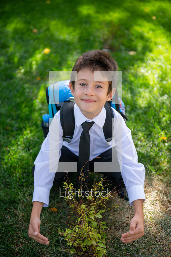 a child in dress clothes and a book bag hugging a tree