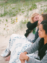 teen girls sitting on the dunes on a beach