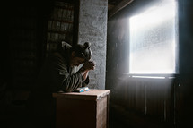 a man praying with head bowed over a Bible