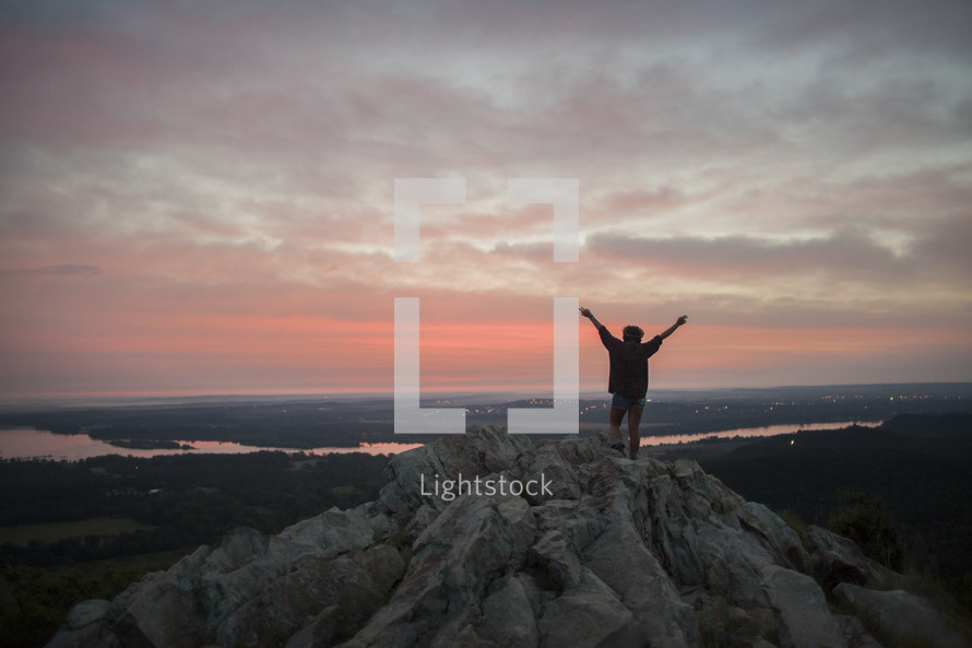 Silhouette of a person with arms raised standing on a mountain at sunrise.