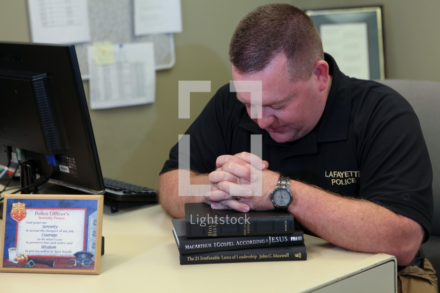 police officer in prayer over a Bible