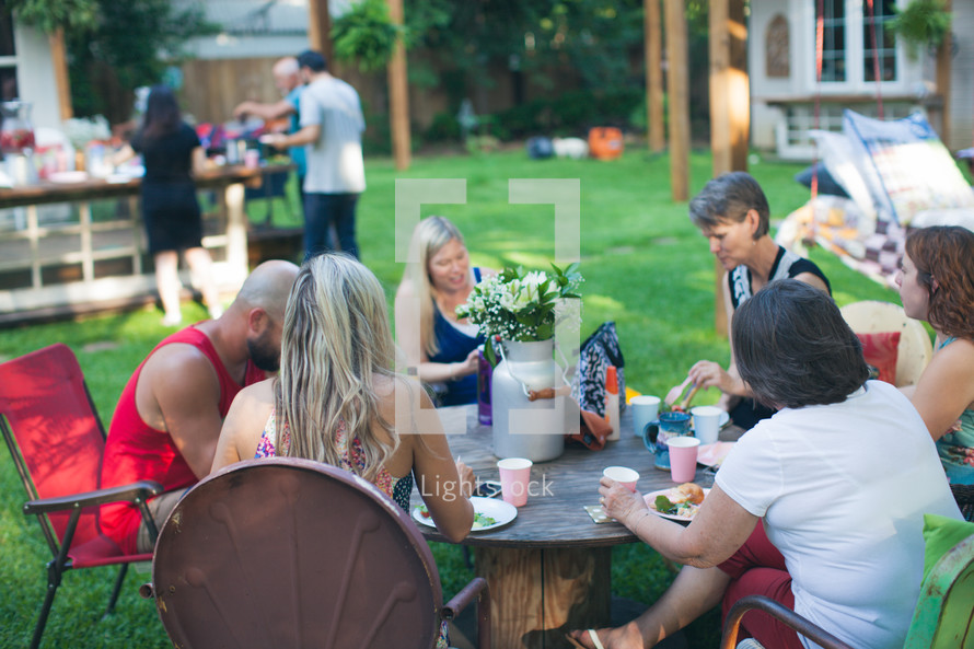 people eating around a table at an outdoor party