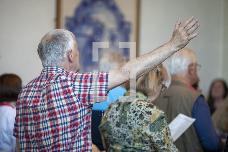 an elderly man with hand raised in praise during a worship service
