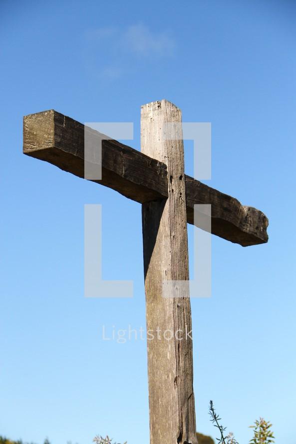 A wooden cross against a blue sky.
