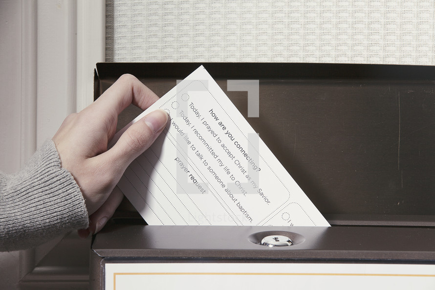 Hand placing a card in a box on a door.