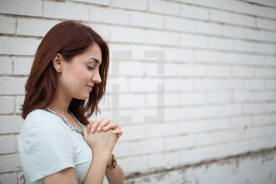 a young woman with praying hands