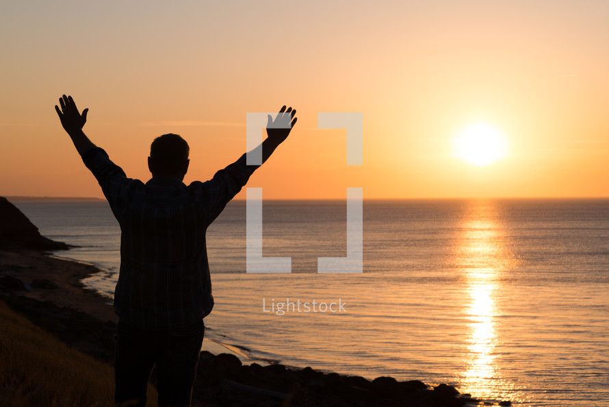 a man standing on a shore at sunset with raised arms