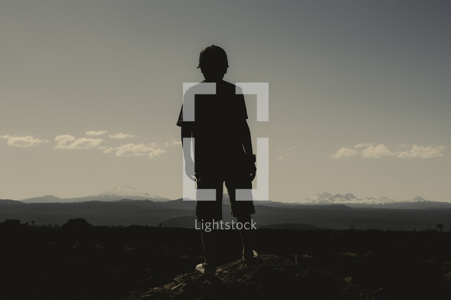 Silouette of a young boy facing forward toward mountains | Vision | Dream | Imagine | Standing