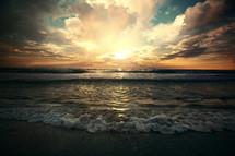 tide washing onto a shore at sunrise