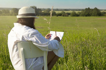 a woman sketching a drawing in a field