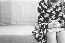 teen girl sitting on a couch praying over a Bible