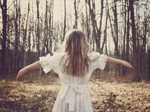 a girl in a dress standing with arms out-stretched in front of a forest