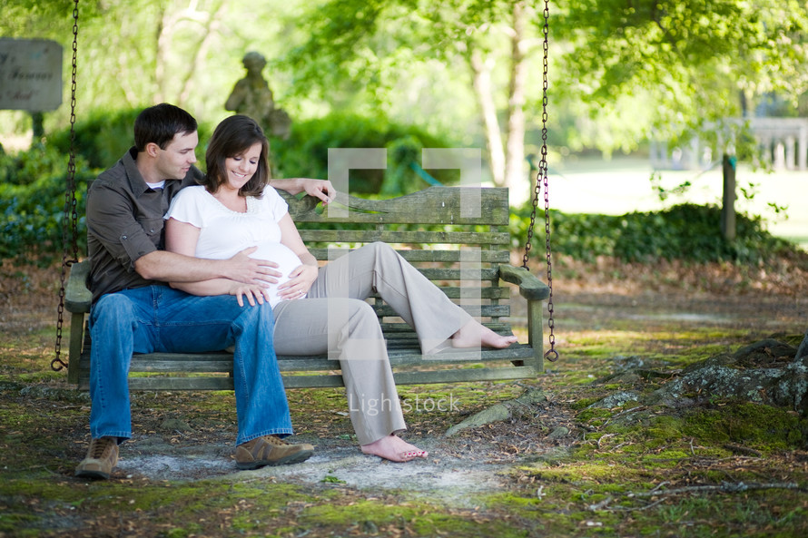 expecting couple sitting on a park bench