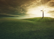 glowing cross on a grassy hill
