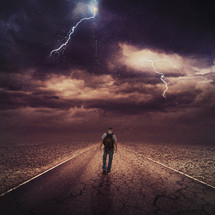 man on a journey walking down a road under a storm