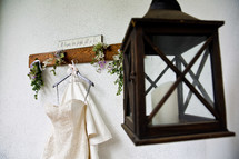 wedding dress hanging on a hook and lantern