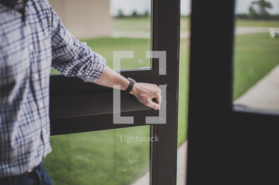 man holding open a door to a church
