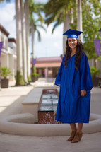 a graduate in cap and gown standing under palm trees
