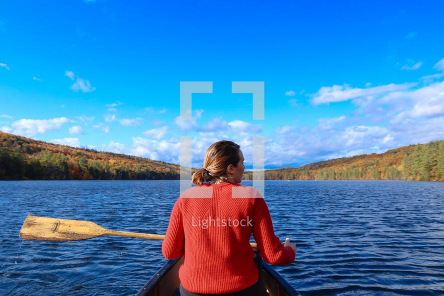 a woman paddling a canoe on a lake