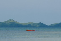 An empty red row boat on the water near mountains.