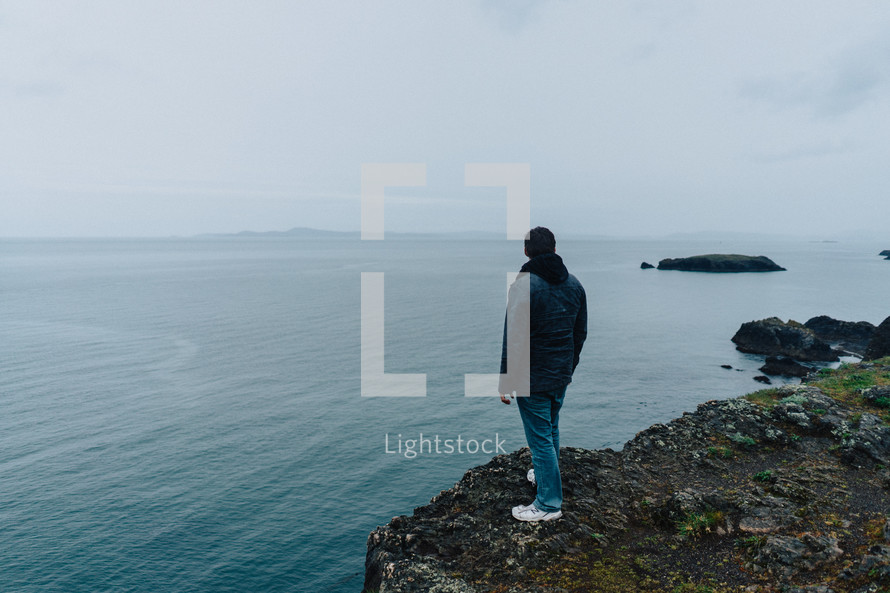 man standing at the edge of a cliff looking out into the ocean