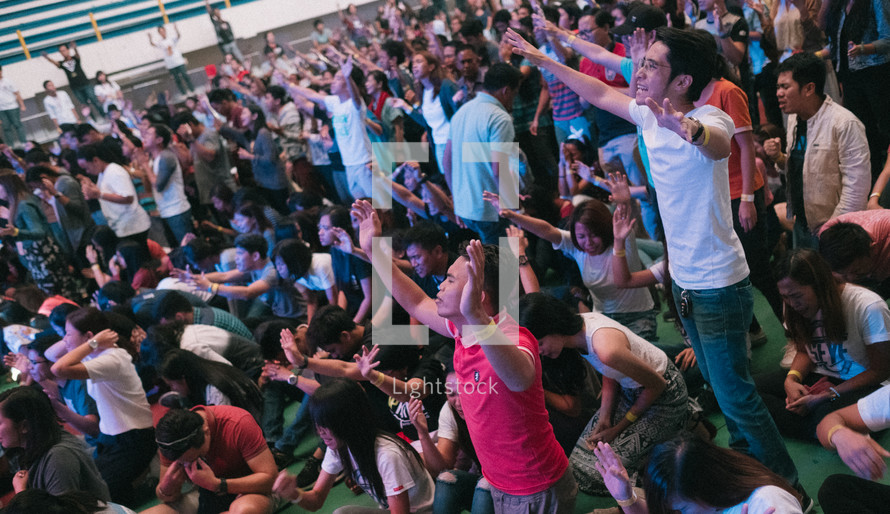 crowds with hands raised in praise