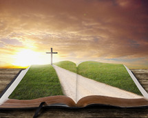 Road leading to the cross on an open Bible at sunrise.
