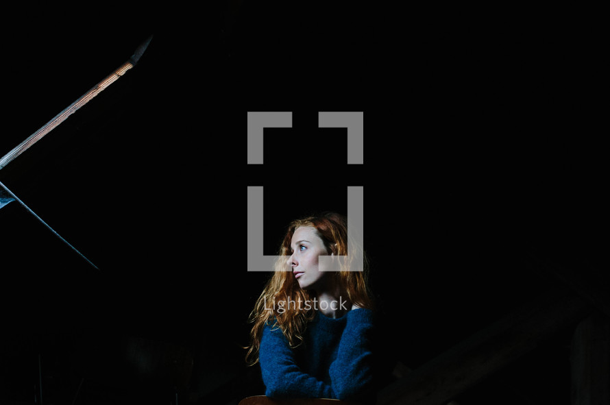 side profile of a woman sitting in darkness