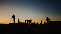 silhouettes of people on a mountaintop at sunset