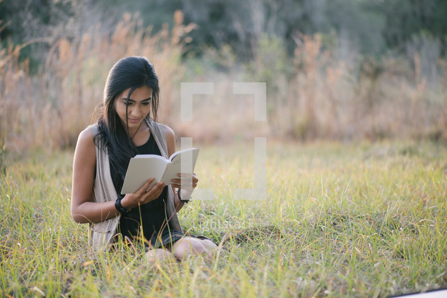 young woman sitting in grass studying scripture