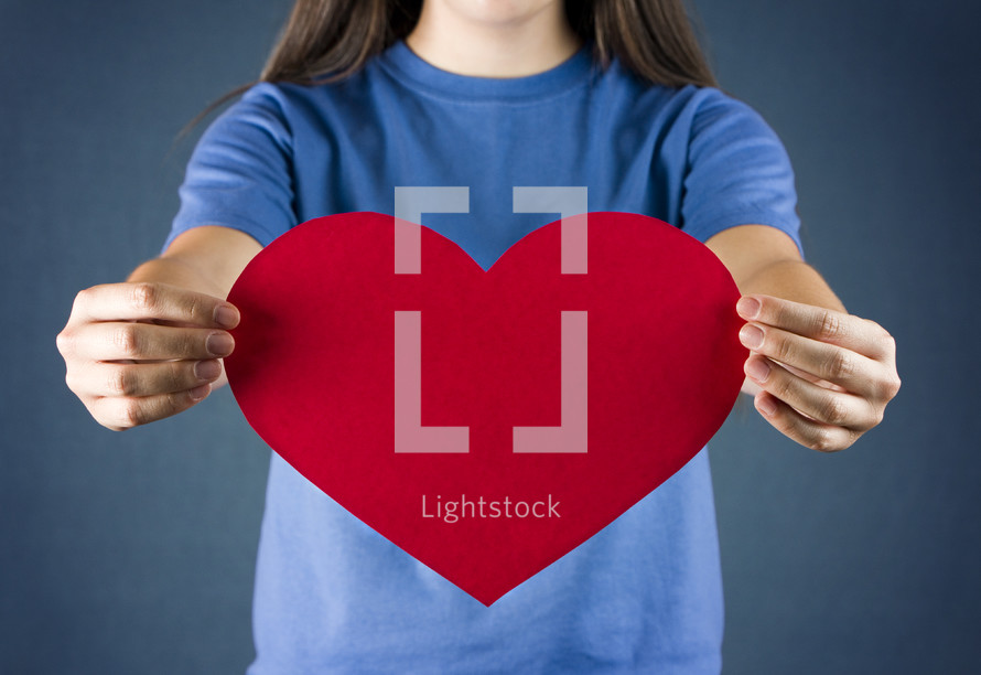 A teenage girl holding out a red heart.  Plenty of space to add your own text.