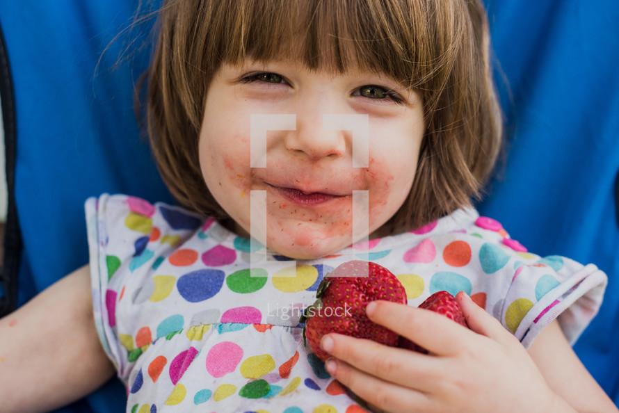 toddler girl eating strawberries