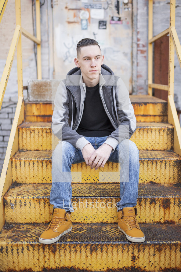 a young man sitting on rusty stairs