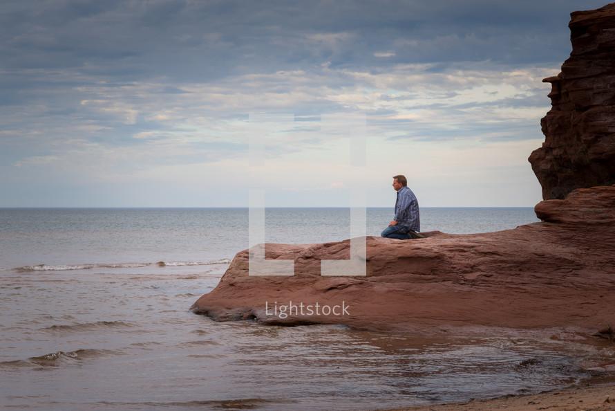 a man kneeling on a beach