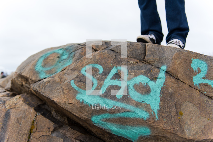 woman standing on a rock with the word sad spray painting on the side