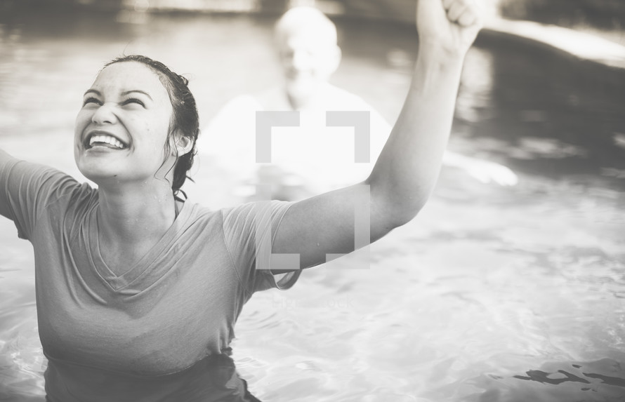 woman with raised hands after a baptism