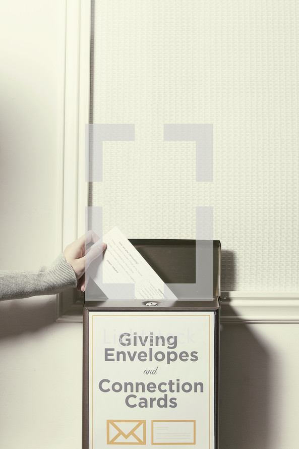 Hand placing an envelope in the donation box.