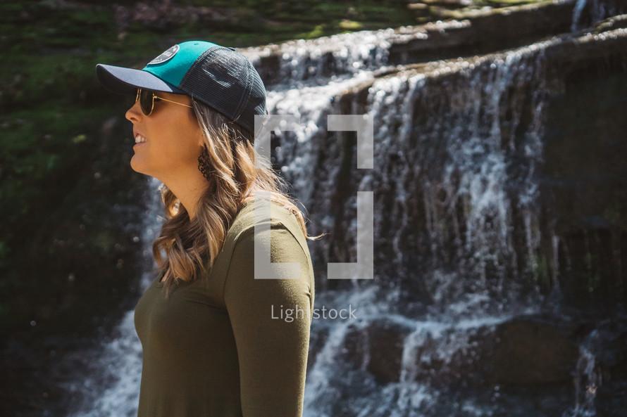 a woman standing outdoors wearing a ball cap