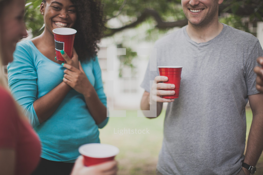 friends in conversation at a cookout holding red cups