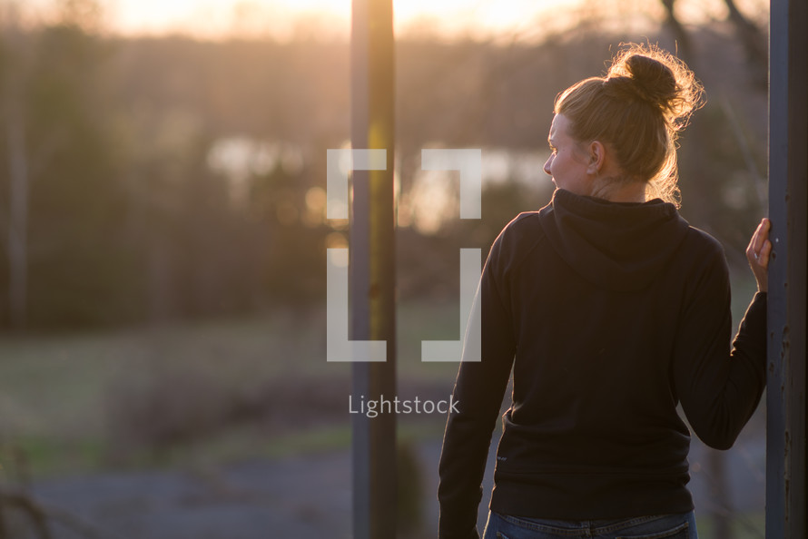 teen girl standing outdoors at sunset
