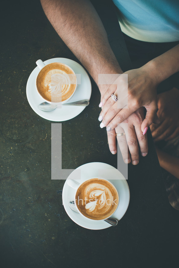 a couple holding hands and coffee cups
