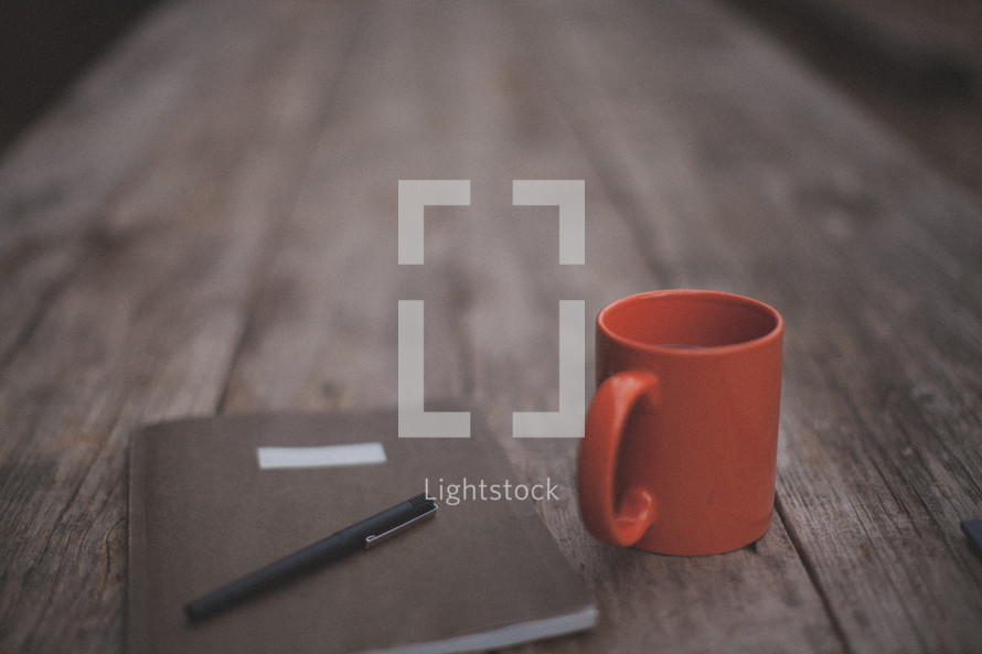 A pen and notebook next to an orange coffee mug on a wooden table