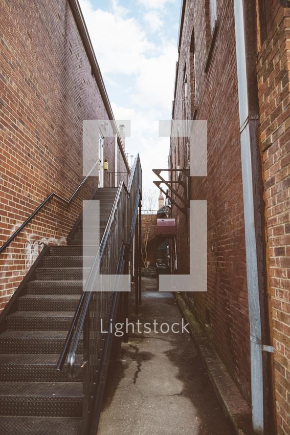 Stairway in an alley between two brick buildings.
