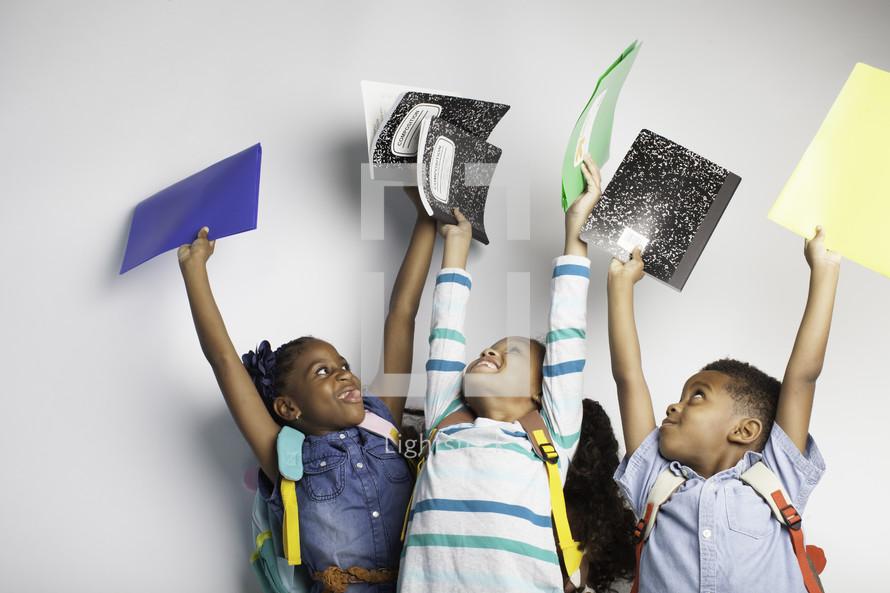 children holding up notebooks