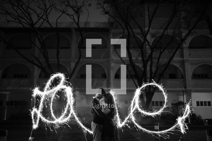 couple kissing in front of the word love in sparklers