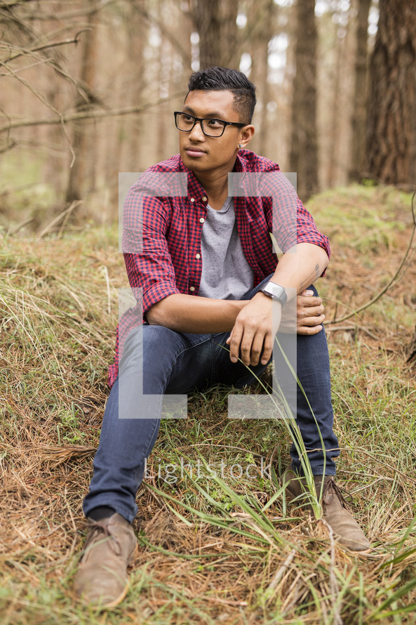 a portrait of a young man sitting on a hill in a forest