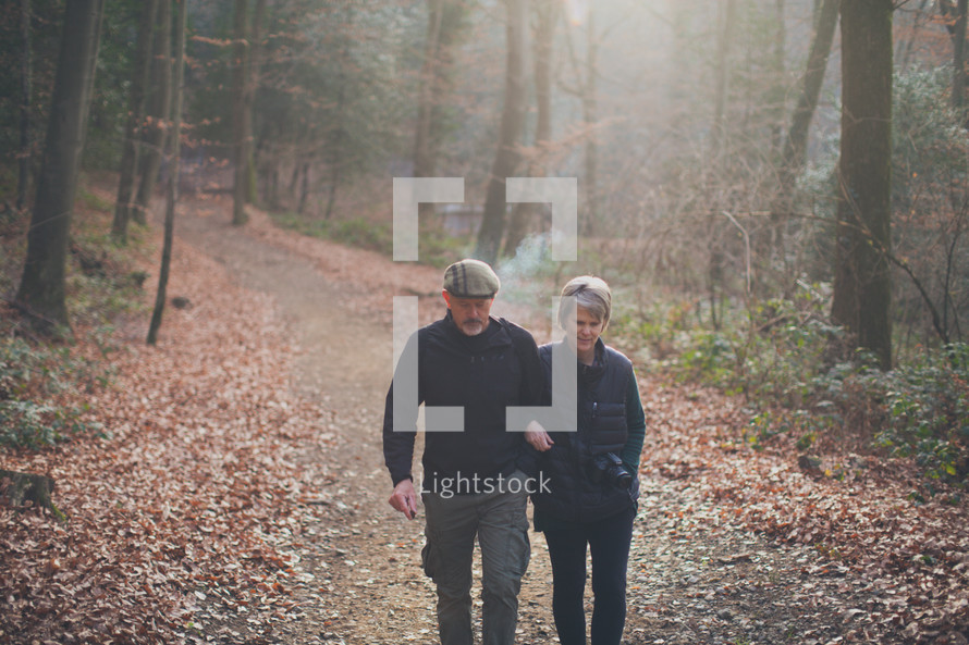 couple walking arm in arm on a nature trail