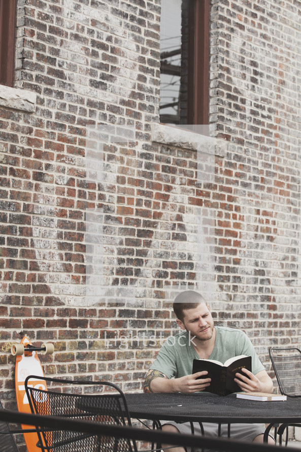 man reading a Bible sitting at an outdoor cafe