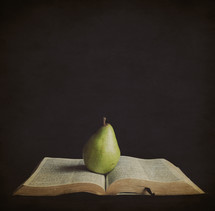 pear resting on the pages of a Bible