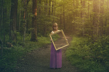 woman holding a mirror in a forest